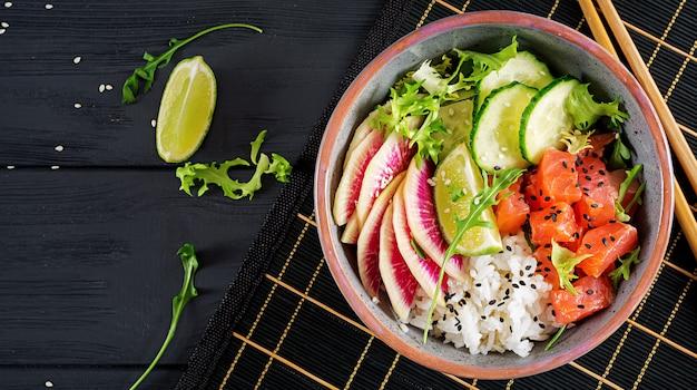 Bol à poisson en saumon hawaïen avec riz, concombre, radis, graines de sésame et citron vert.