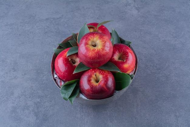 Un bol de pommes avec des feuilles sur la surface sombre