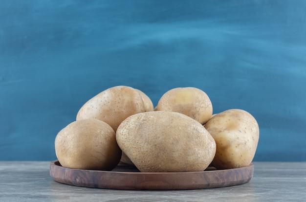 Un bol de pommes de terre mûres sur la table en marbre.