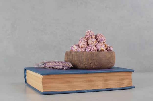 Un bol de pop-corn aromatisé et une tige de blé purpe sur un livre sur fond de marbre.