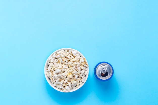 Bol avec pop-corn et une canette de boisson sur fond bleu. le concept de regarder des films et des émissions de télévision préférées, des compétitions sportives. mise à plat, vue de dessus.