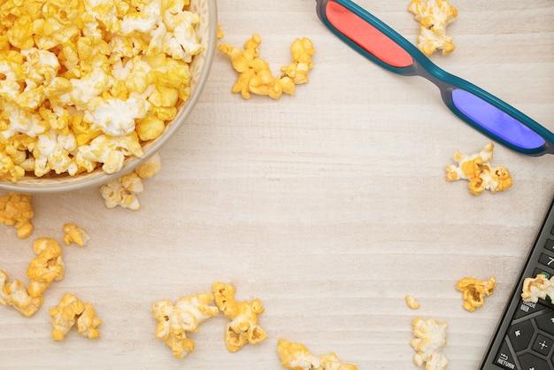 Un bol de pop-corn, des lunettes de cinéma 3d et une télécommande sur un fond en bois blanc.