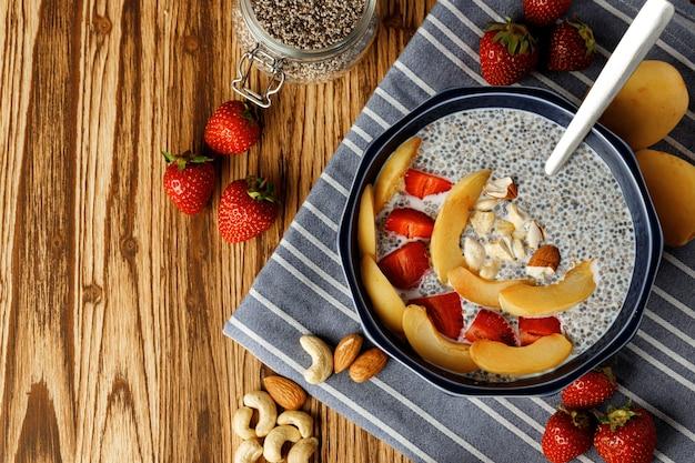 Bol de pouding de chia avec des morceaux d'abricots et de fraise