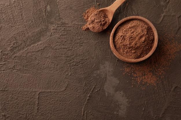 Bol avec poudre de cacao et cuillère sur brun, espace pour le texte