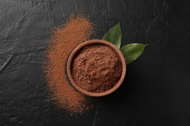 Bol avec poudre de cacao et feuilles sur fond noir, vue de dessus