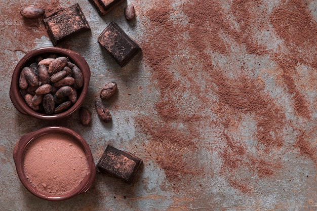 Bol de poudre de cacao et de haricots avec des morceaux de chocolat