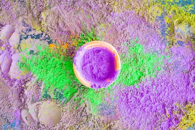 Bol de poudre de holi violet sur le fond texturé de couleur mélangée