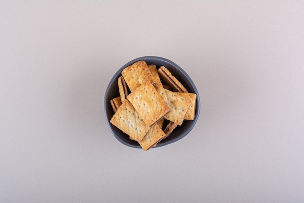 Bol profond avec des biscuits fourrés au chocolat sur fond blanc. photo de haute qualité