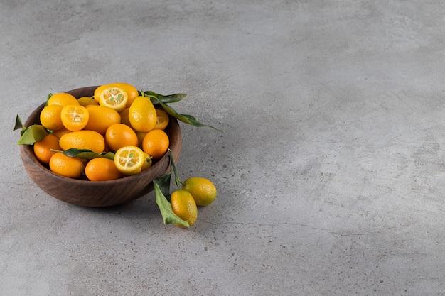 Bol profond de kumquats juteux frais sur la surface de la pierre