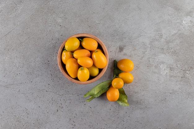 Bol profond de kumquats juteux frais sur table en pierre.