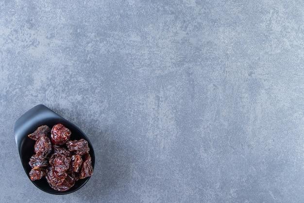 Un bol de prune séchée, sur le fond de marbre.