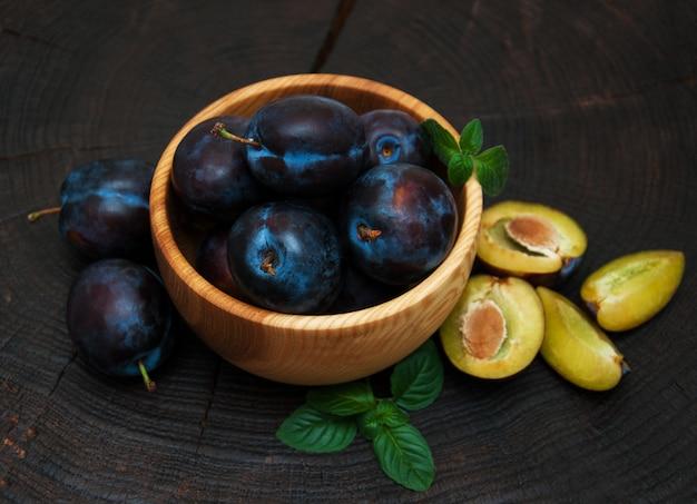 Bol de prunes aux feuilles vertes