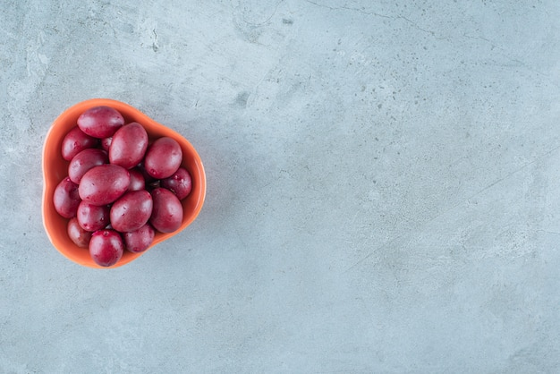Un bol de prunes fermentées , sur la table en marbre.