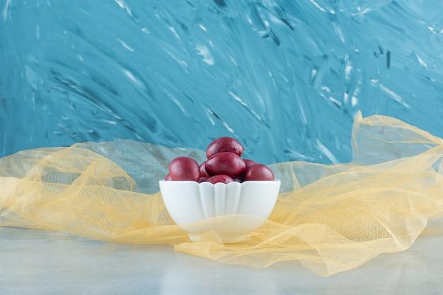Un bol de prunes fermentées sur tulle, sur la table bleue.