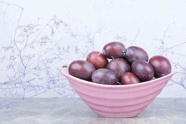 Bol de prunes fraîches sur table en pierre.