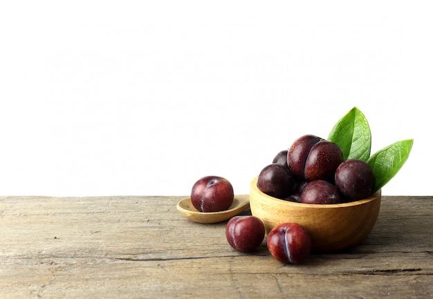 Bol de prunes mûres sur table en bois
