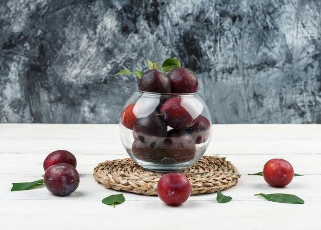 Un bol de prunes sur un napperon en osier sur un fond de marbre bleu foncé et planche de bois blanc. fermer.