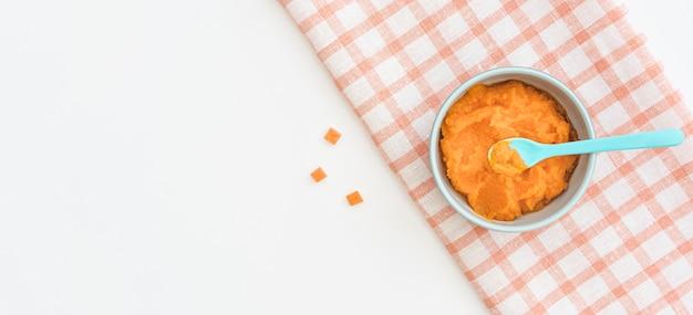 Bol avec purée de bébé carotte avec copie-espace