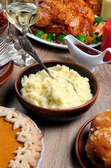 Un bol de purée de pommes de terre sur une table parmi la dinde cuite par tarte à la citrouille