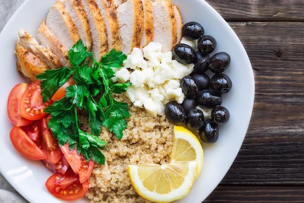 Bol de quinoa au poulet sain avec tomates cerises, olives feta et persil sur fond de bois