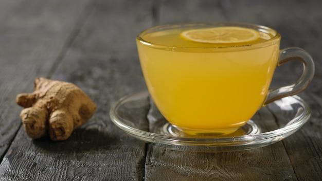 Bol de racine de gingembre et d'agrumes boire sur une table en bois noire.