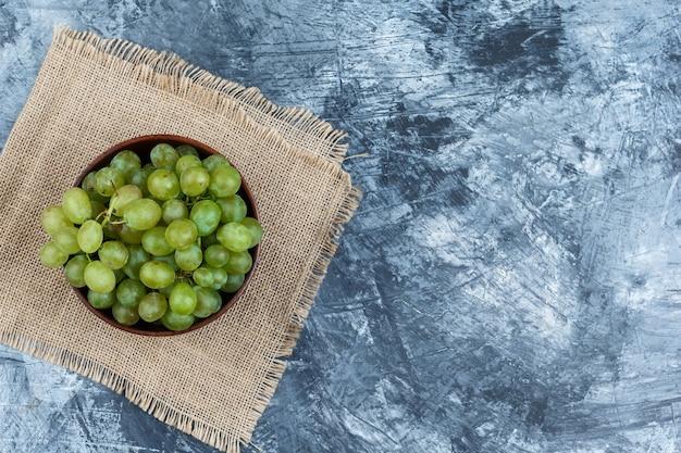Un bol de raisins blancs sur un napperon sur fond de marbre bleu foncé, à plat.