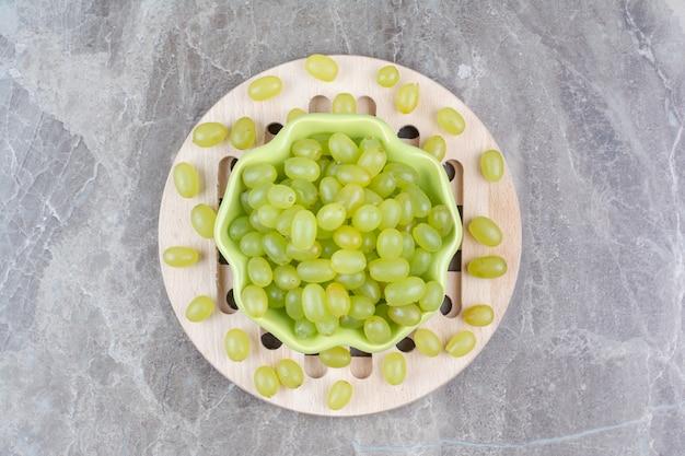 Bol de raisins verts sur morceau de bois.