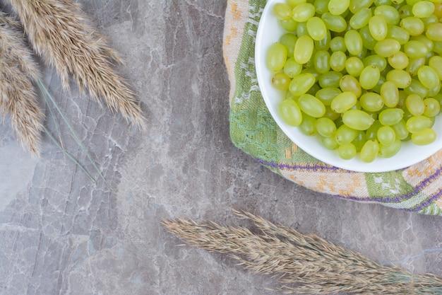 Bol de raisins verts sur nappe colorée.