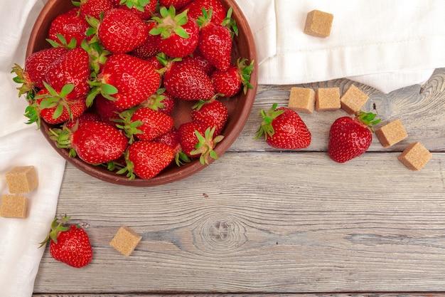 Bol de récolte de fraises sur table en bois close up