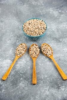 Un bol rempli de haricots blancs crus avec des cuillères en bois.
