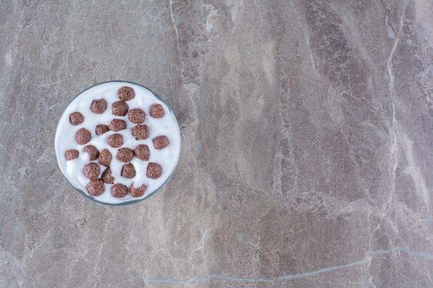 Un bol rempli de yaourt sain et de petites boules de céréales au chocolat.