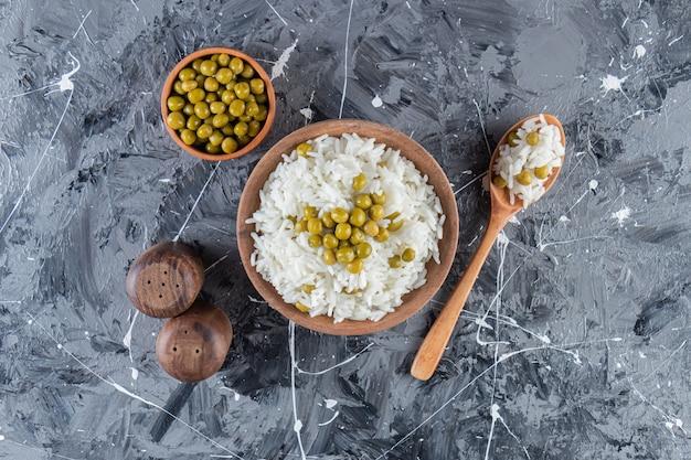 Bol de riz blanc cuit à la vapeur avec des pois verts sur fond de marbre.