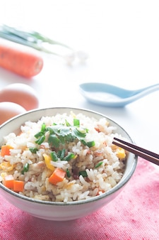 Bol de riz frit, carotte et œuf sur tissu rose, cuillère, baguettes et ingrédients pour l'arrière-plan