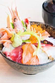 Bol de riz japonais avec des fruits de mer sashimi sur le dessus