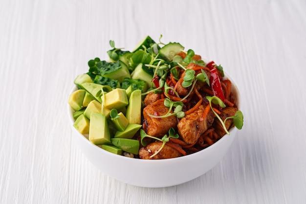 Bol avec riz, poulet, avocat, concombre, carotte, poivron et pousses de pois sur une table en bois blanc