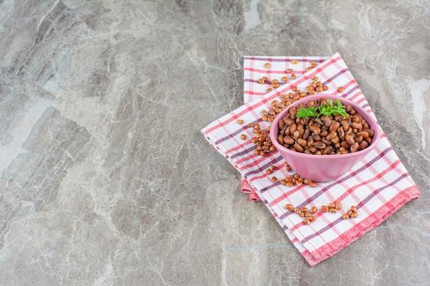 Bol rose de haricots bouillis avec nappe sur une surface en marbre.