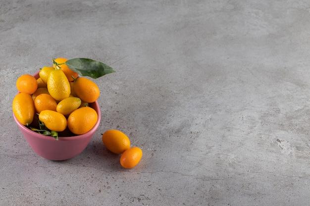 Bol rose de kumquats juteux frais sur la surface de la pierre