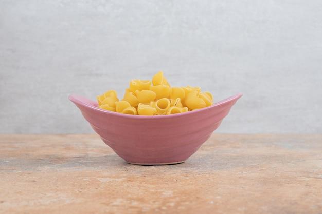 Un bol rose de macaronis non préparés sur un espace en marbre.