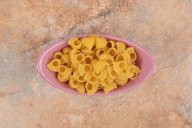Un bol rose de macaronis non préparés sur fond de marbre. photo de haute qualité