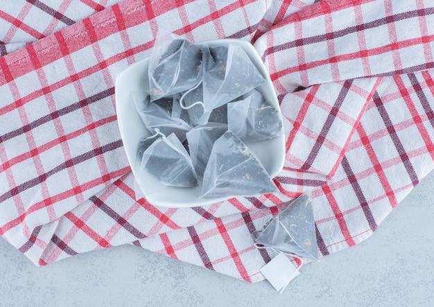 Un bol de sachets de thé sur une serviette sur du marbre.