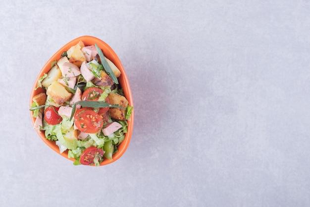 Bol de salade fraîche avec des saucisses sur fond de marbre.