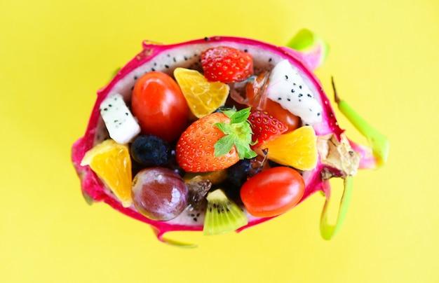 Bol de salade de fruits servi dans un fruit du dragon et des légumes des aliments biologiques sains fraises orange kiwi bleuets raisins ananas tomate citron fruits d'été frais fruits tropicaux sur jaune