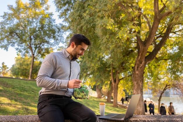 Un bol de salade sur les jambes d'un jeune travailleur et étudiant bien habillé à l'aide de son ordinateur portable dans un parc par une journée ensoleillée.