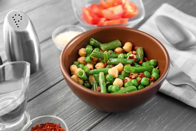 Bol avec salade de légumes frais sur table en bois.