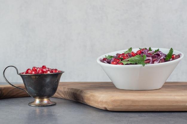 Bol de salade de légumes sur planche de bois avec graines de grenade. photo de haute qualité