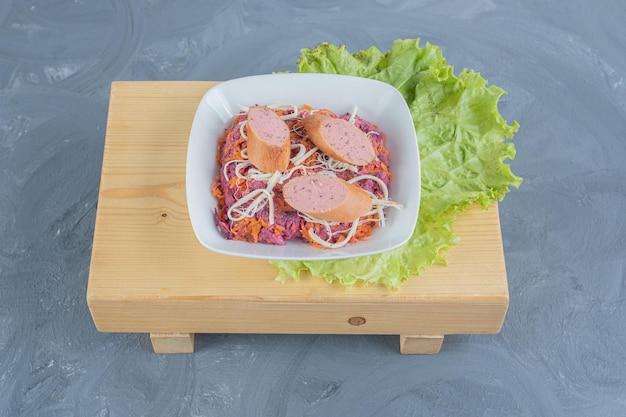 Bol de salade de noix et de betteraves sur une planche de bois avec des feuilles de laitue, garni de saucisses et de fromage sur une surface en marbre.