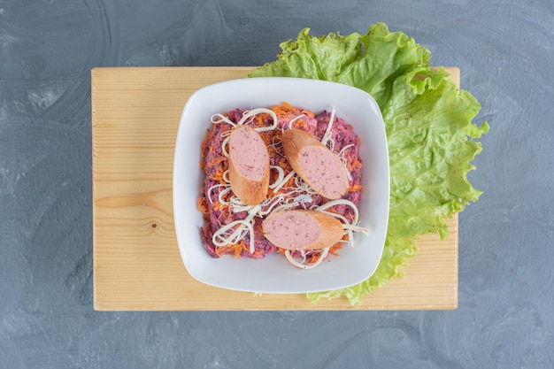 Bol à salade de noix et de betteraves sur une planche de bois avec des feuilles de laitue, garni de saucisses et de fromage sur une table en marbre.