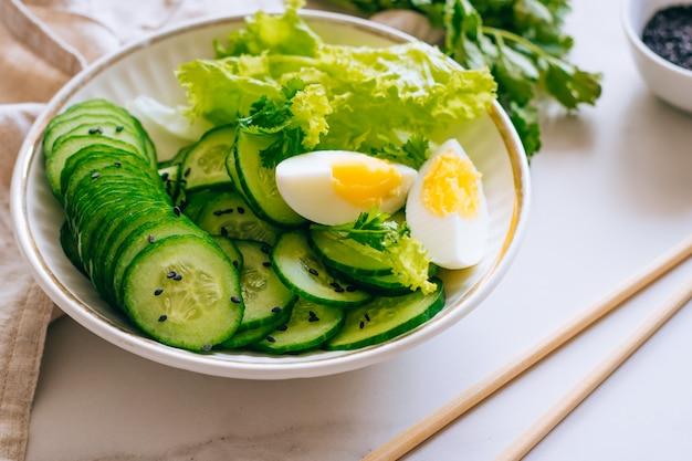 Bol santé, salade de concombre aux œufs et coriandre sur fond de marbre