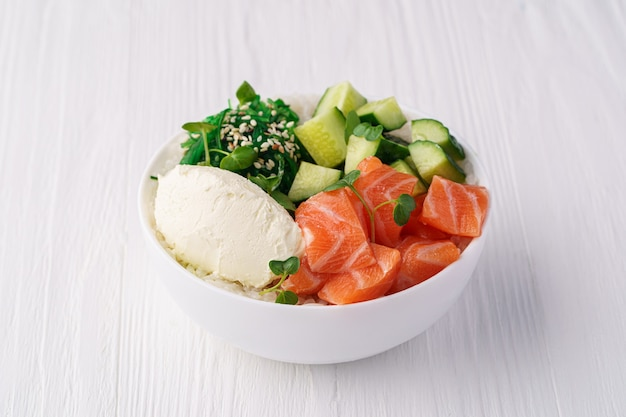 Bol avec saumon, riz, chukka, fromage à la crème, concombre, graines de sésame et pousses de pois sur une table en bois blanc