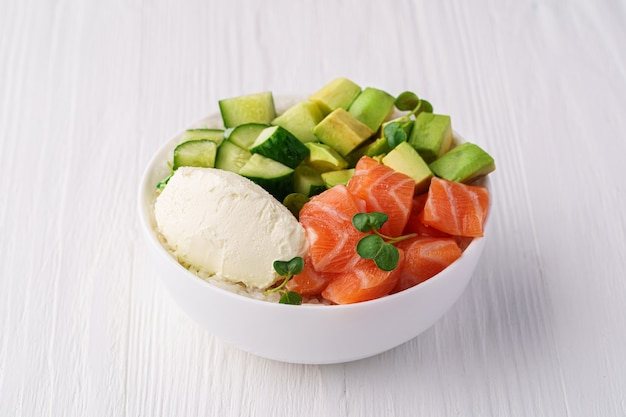 Bol de saumon, riz, fromage à la crème d'avocat, concombre et pousses de pois sur une table en bois blanc